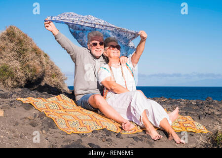 Adults caucasian couple having fun and enjoy the outdoor leisure activity together in the nature near the ocean - hippy freedom style and nice lifesty - Stock Photo