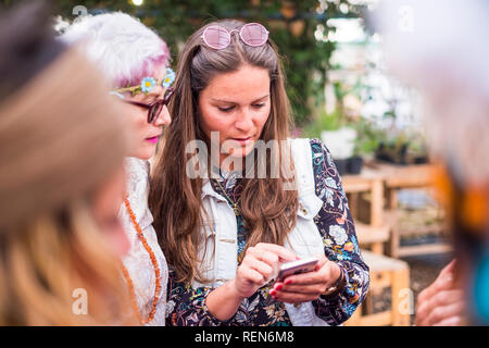 Hippy fashion style trendy group of mixed ages caucasian women using technology modern phone together - beautiful females with coloured dress and clot - Stock Photo