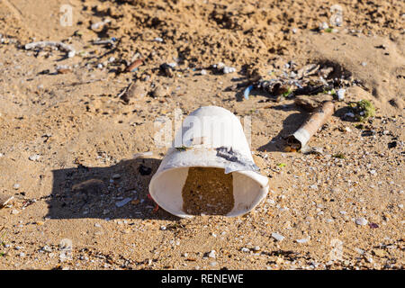 Disposable tableware glass on sandy beach after tide. The concept of plastic pollution of world ocean, close up - Stock Photo