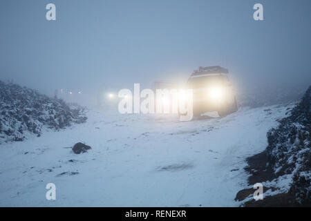 A convoy of off-road vehicles navigate a snow covered track in heavy fog. Houndkirk Road, Peak District National Park, Sheffield, South Yorkshire, Eng - Stock Photo