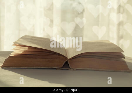 Romantic still life of open old book under warm sunlight and heart bokeh on the background - Stock Photo