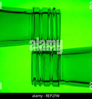 Two beer bottle necks on a green background - Stock Photo