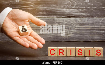 Businessman holds in his hands a cube with the image of the dollar and the word crisis. Fall business. Financial collapse. Income reduction. Bankruptc - Stock Photo