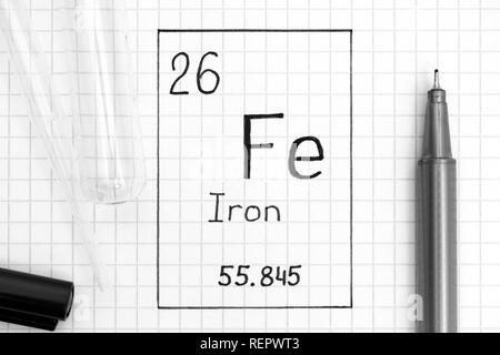 The Periodic table of elements. Handwriting chemical element Iron Fe with black pen, test tube and pipette. Close-up. - Stock Photo