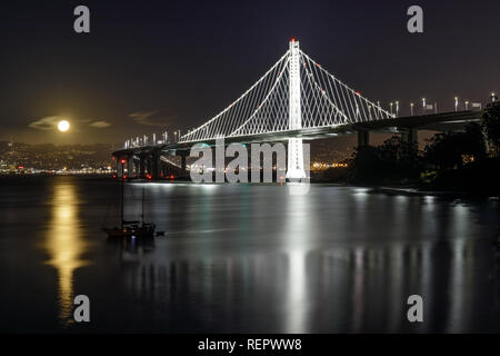 Full moon rising over the new eastern span of the San Francisco-Oakland Bay Bridge at night. - Stock Photo