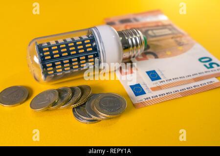 Led Light Bulb and european banknotes and coins. E27 Corn bulb - Stock Photo