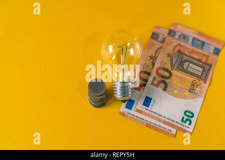 Light Bulb and european banknotes and coins. E27. Coiled tungsten filaments. - Stock Photo
