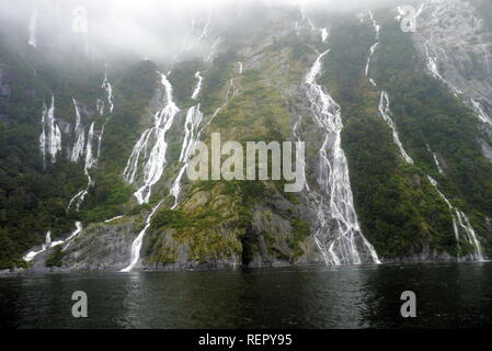 Hundreds of waterfalls flowing from the mountains during the rainstorm in Fiordland National Park, New Zealand - Stock Photo