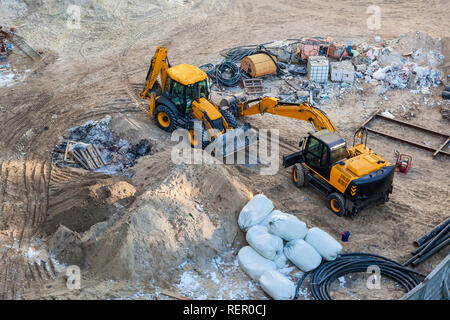 Two yellow excavators on the construction site waiting for the start of work - Stock Photo