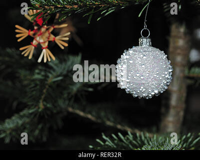 close-up of white christmas bauble at spruce tree with straw stars in background - Stock Photo