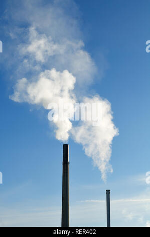 chimneys in industrial area emitting white smoke in front of blue sky - Stock Photo