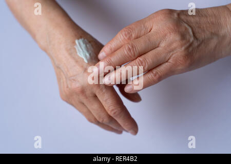 Skin care. Elderly woman applies Cream On Her Hands. Beauty product. - Stock Photo