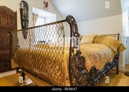 3/4 size bed with 200 year old French metal grill style headboard and footboard in guest bedroom inside an old 1839 Canadiana fieldstone style house - Stock Photo