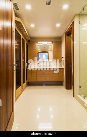 Basement bathroom with white marble floor, bamboo wood vanity and sauna room inside luxurious stained cedar and timber wood home - Stock Photo