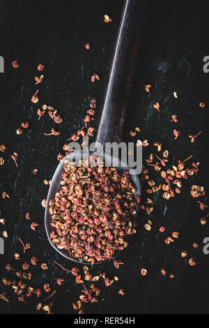 Directly above shot of Sichuan peppercorns on black background - Stock Photo