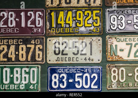 Colourful collection of vintage Quebec automobile licence plates on garage wall inside an old 1927 Canadiana cottage style home - Stock Photo