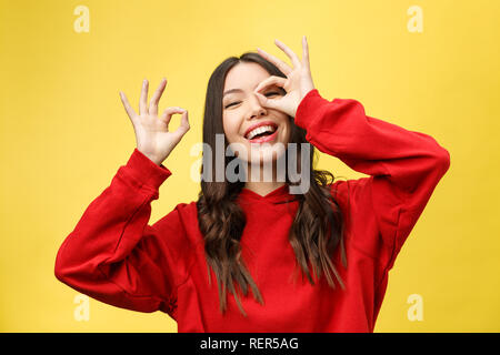Close up portrait of beautiful joyful Caucasian female smiling, demonstrating white teeth, looking at the camera through fingers in okay gesture. Face expressions, emotions, and body language - Stock Photo