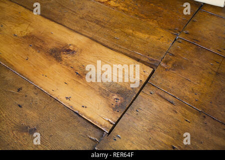 Close-up of red pinewood floorboards in attic room inside an old 1809 French regime cottage style home - Stock Photo