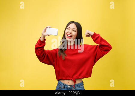 Smiling young girl making selfie photo on smartphone over yellow background - Stock Photo