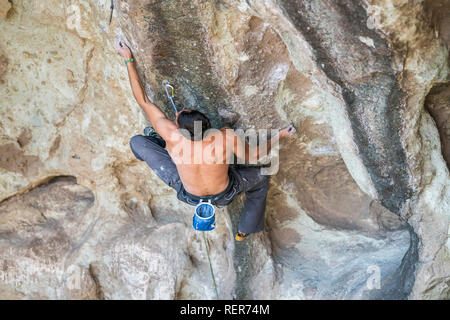 Practicing rock climbing extreme sport inside Andes mountains at a rock cliff. One male climber make the hard movements with tenacity and confidence