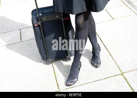 Business woman's legs and overnight bag - Stock Photo