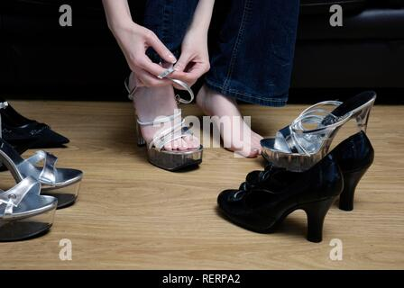 Feet of a young woman surrounded by several high heel shoes - Stock Photo