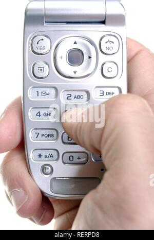 Close up of hand using mobile phone keypad to send text messages - Stock Photo