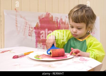 A two year old girl in a plastic smock painting in a playroom with a brush and roller - Stock Photo