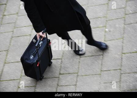 Young woman, partial view, rushing with an overnight case - Stock Photo