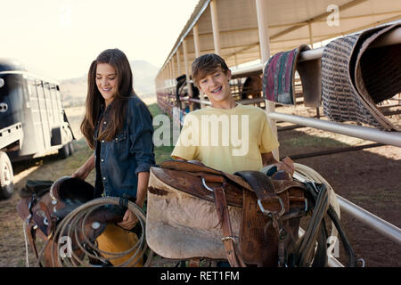 Portrait of two smiling teenagers holding horse riding saddles. - Stock Photo