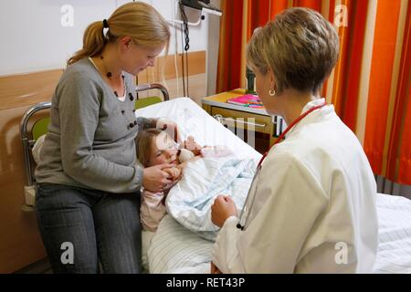 Doctor talking to a young patient, seven years old, and her mother at the bedside in a hospital - Stock Photo