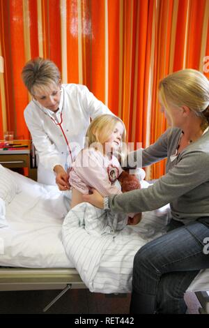 Doctor examining a young patient, seven years old, supported by the mother, at the bedside in a hospital - Stock Photo