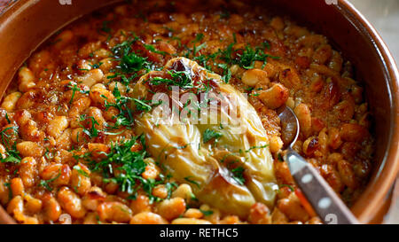 Serbian National Cuisine dish Baked Beans or Prebranac served with green paprika and parsley in a terracotta pot - Stock Photo