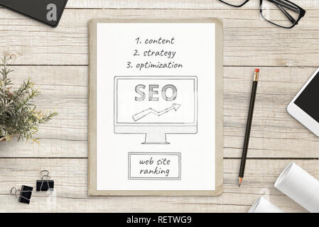 Search engine optimization sketch on white paper surrounded with office supplies. SEO web site concept. - Stock Photo