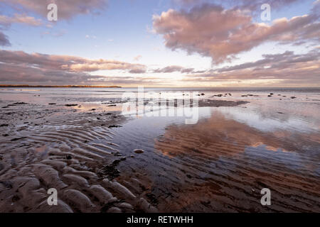 Scenic view over a coastal landscape, in the foreground sand ribs, above it some colored clouds, which are reflected in the shallow water - Location:  - Stock Photo