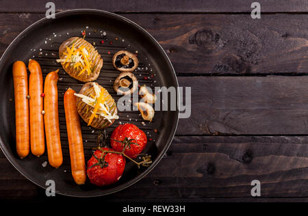 Baked stuffed potatoes with cheese, cheddar, dill, wiener sausages and cherry tomatoes in a pan on black wooden background with copy space. - Stock Photo