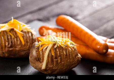 Baked stuffed potatoes with cheese, cheddar, dill and wiener sausages on wooden table - Stock Photo