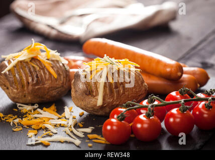 Baked stuffed potatoes with cheese, cheddar, dill, wiener sausages and cherry tomatoes on wooden table - Stock Photo