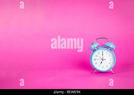 Beautiful retro blue pastel alarm clock on a vibrant pink background - Stock Photo