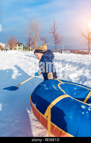 The little boy pulls the tubing. In hands of holding a spatula. In winter, the city plays on a roller coaster a happy child. - Stock Photo