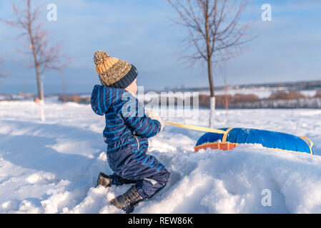 The little boy pulls the tubing. In the hands of holding a spatula. In winter, the city plays on a roller coaster a happy child. - Stock Photo