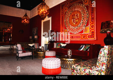 Red interior with velvet and ancient furniture, big glass lamps, Spain - Stock Photo
