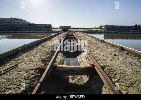 Abandoned rusty mine railway next to river - Stock Photo