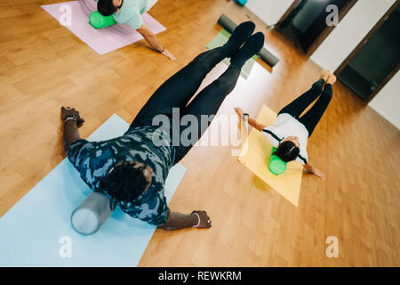 People doing exercises with foam rollers in the gym - Stock Photo