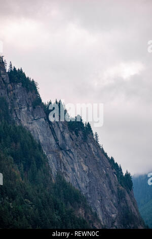 Steep rocky cliff of mountain surrounded by trees on overcast sky background. - Stock Photo