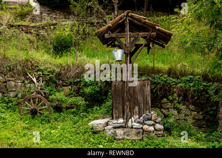 A wooden well in the village of Rsovci on the Old mountain ( Stara planina ) in Serbia, beside him there is a plow for the plowing of the soil. - Stock Photo