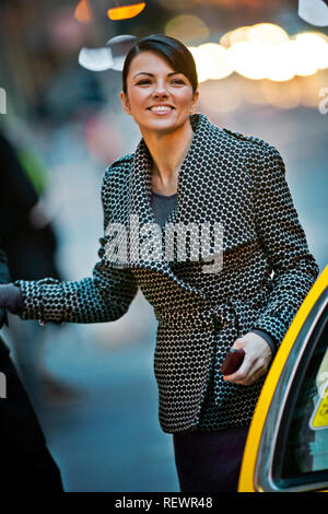 Smiling young businesswoman gets out of a yellow taxi. - Stock Photo