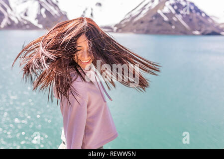 Girl looking at the amazing mountain view. with messy windy hair Turquoise waters of 'Embalse del Yeso' (Cast Lake) inside Central Andes mountains - Stock Photo