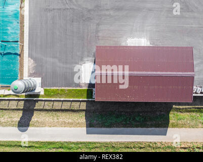 brown metal corrugated roof of warehouse. industrial area. aerial view - Stock Photo