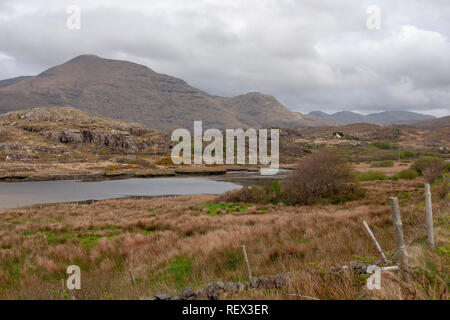 Fence and field beside tidal inlet in Irish field, County Mayo with Mweelrea in the background. - Stock Photo